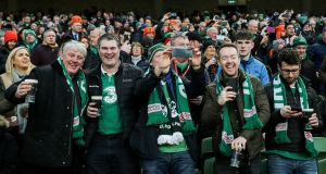 Ireland fans drink pints in the stand during the Six Nations opening match win over Scotland. Photo: Gary Carr/Inpho