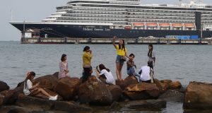 People take pictures on rocks next to the docked Westerdam cruise ship in Sihanoukville, Cambodia on Tuesday as authorities checked if any passengers that remained could have the Covid-19 coronavirus. Photograph: Tang Chhin Sothy/AFP  via Getty Images)
