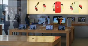Employees wear face masks at Apple Store in Beijing.  Photograph:  Lintao Zhang/Getty Images