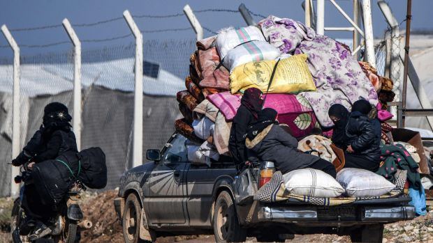 Women and children ride in the back of a truck loaded with belongings, as they pass through the town of Jindayris, near the Syrian-Turkish border, at the weekend. Photograph: Rami al Sayed/AFP via Getty Images