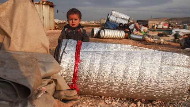 A child stands behind a rolled-up thermal insulation foil at a camp for displaced Syrians east of Sarmada in Idlib province on Sunday, as people prepare to flee the camp. Photograph: Aaref Watad/AFP via Getty Images