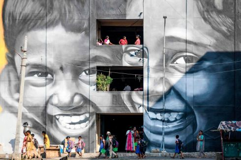 Residents walk past a mural painted on a building at a slum clearance board residential community in Chennai. Photograph: Arun Sankar/AFP