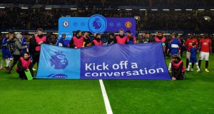 Chelsea and Manchester United players pose with a 'Heads Up' campaign banner at Stamford Bridge. Photograph: Getty Images