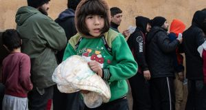 A displaced Syrian girl carries a bag of bread in a stadium which has been turned into a makeshift refugee shelter on Wednesday, in Idlib, Syria. Photograph:  Burak Kara/Getty Images