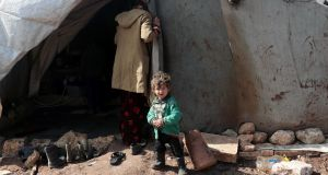 An internally-displaced Syrian child stands outside a tent at a makeshift camp in Azaz, Syria, on  Thursday. Photograph:  Khalil Ashawi/Reuters