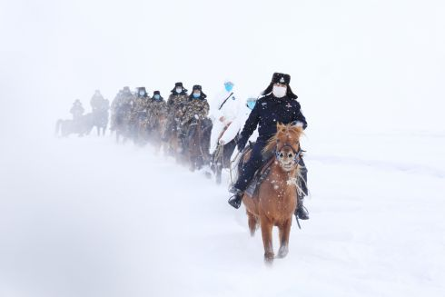 CHINA: Border authorities travel through the snow to inspect a mountainous border area and to provide information of Covid-19 (the coronavirus originated in China) to residents in a remote area of Altay, Xinjiang province, China. Photograph: A Ran/EPA