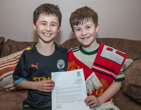 CROSSING THE DIVIDE: Manchester United fan Daragh Curley (10) and his brother Dylan with his letter from Liverpool manager Jürgen Klopp. The German replied to Daragh after the Donegal schoolboy wrote to him asking him to ensure Liverpool stop winning. Photograph: North West Newspix