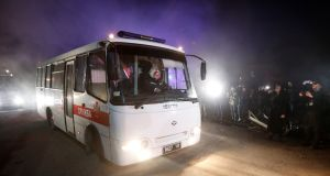 Buses transporting evacuees from coronavirus-hit China's Hubei province drive past demonstrators during a protest against their arrival. Photograph: Vlaentyn Ogirenko/Reuters