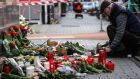 People place flowers and candles at a makeshift memorial for the racist terror attacks in Hanau on Thursday. Photograph: Armando Babani/EPA