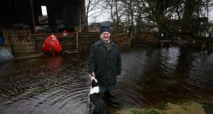 Jim Connolly  with his dog Judy in his flooded back garden on his farm in Newtownflood, outside Athlone, Co Westmeath. Photograph: Laura Hutton/The Irish Times
