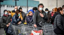 People wearing sanitary masks queue outside a supermarket in Casalpusterlengo, Northern Italy on Sunday. Photograph: Claudio Furlan/Lapresse via AP.