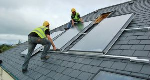 Workers install solar panels on a roof.  Photograph: courtesy of Construct Ireland