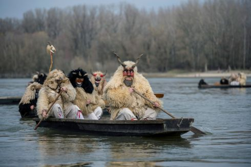 Costumed revellers arrive by boat crossing the river Danube for the Busho parade in Mohacs, Hungary, on closing day of  the carnival. Photograph: Tamas Soki