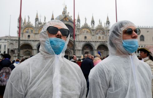 Tourists wear protective face masks at Venice Carnival. The last two days of the event as well as Sunday night's festivities have been cancelled because of an outbreak of coronavirus, in Venice. Photograph: Manuel Silvestri/Reuters
