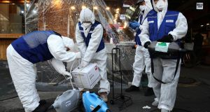 Disinfection professionals wearing protective gear prepare to disinfect against the coronavirus (COVID-19) at a traditional market on February 24th in Seoul. Photograph:  Chung Sung-Jun/Getty Images