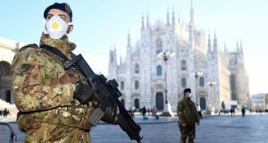 Military officers wearing face masks stand outside Milan's Duomo cathedral. Photograph: Flavio Lo Scalzo/Reuters