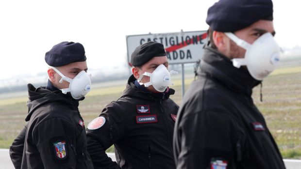 Carabinieri officers stand guard outside the town of Castiglione D'Adda, which has been closed by the Italian government due to a coronavirus outbreak. Photograph: Guglielmo Mangiapane/Reuters