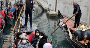 Tourists wear protective face masks in a gondola on Sunday. Photograph: Manuel Silvestri/Reuters