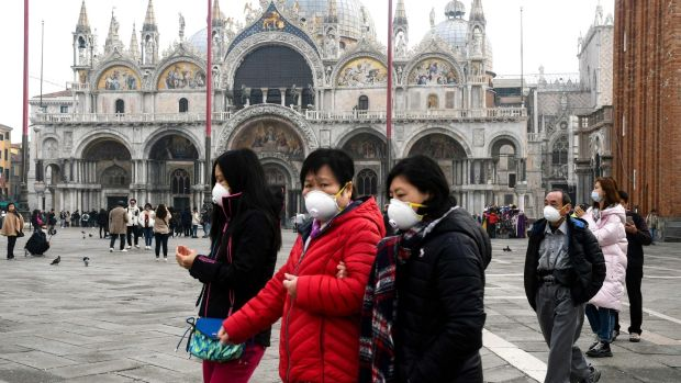 Tourists wearing protective facemasks visit the Piazza San Marco, in Venice, on Monday during the usual period of the Carnival festivities which the last two days have been cancelled due to an outbreak of the COVID-19. Photograph: (Andrea Pattaro/AFP via Getty Images)
