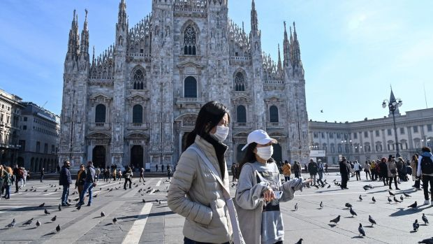Two women wearing a protective facemask walk across the Piazza del Duomo, in front of the Duomo, in central Milan on Monday. Photograph: Andreas Solaro/AFP via Getty Images