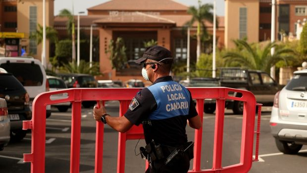 A Spanish police officer sets a barrier blocking the access to the H10 Costa Adeje Palace hotel in Tenerife, Canary Islands, Spain. Photograph: AP Photo