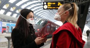 Travellers wear protective face masks at Central Station, Milan, Italy. Photograph: Matteo Bazzi/EPA