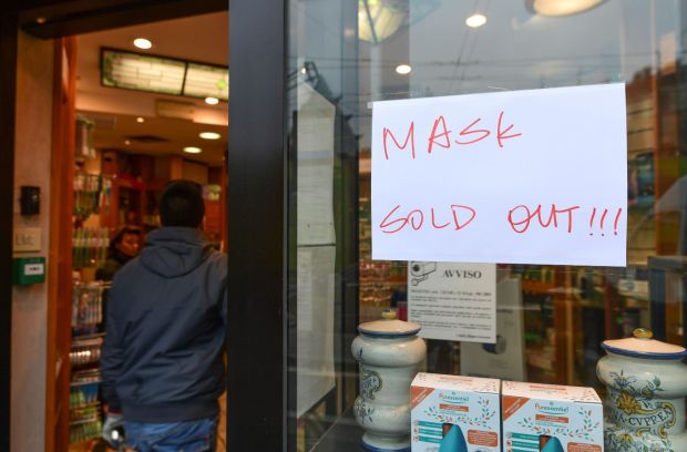 "A man enters a pharmacy displaying on its window a board ""mask sold out"" in the Chinese district of Milan on Tuesday. Photograph: Miguel MEDINA/AFP/Getty Images"