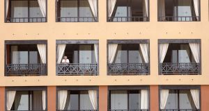 VIRAL LOCKDOWN: A guest looks out from the balcony of a hotel that has been placed under quarantine due to coronavirus, in the town of Adeje, Tenerife, Spain. The hotel was isolated after one of its clients, an Italian tourist, tested positive for the virus. Photograph: EPA