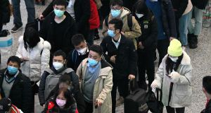 Passengers wearing protective face masks arrive at the Hongqiao railway station in Shanghai. Photograph: Noel Celis/AFP via Getty Images
