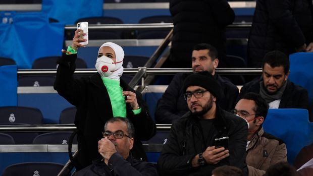 A fan wearing a protective mask against the coronavirus takes a picture before the Uefa Champions League first-leg football match between Real Madrid and Manchester City at the Santiago Bernabeu stadium in Madrid, Spain, on Wednesday. Photograph: Pierre-Philippe Marcou/AFP/Getty