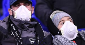 Juventus supporters wear protective face masks as a safety measure against the CoVid-19 novel coronavirus at the Parc Olympique Lyonnais stadium in Decines-Charpieu,  France, on Wednesday, ahead of the Uefa Champions League  football match against Lyon. Photogrtaph: Franck Fife/AFP/Getty