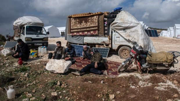 Displaced Syrians sit in front of trucks loaded with their possessions at a newly build camp near village of Atmeh in Idlib. Photograph: Burak Kara/Getty Images