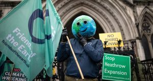 A man celebrates with fellow environmental campaigners outside the royal courts of justice  in London on Thursday. Photograph:  Leon Neal/Getty Images