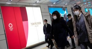 People wearing protective face masks walk past a billboard for the Tokyo Olympics near Shinjuku station in the city on Thursday. Photograph: Athit Perawongmetha/Reuters