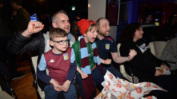 Aston Villa fan club vice-chairman James Mahon and son Leo with chairman Philip Drew and his son Nathan watch a Premier League match in Temple Bar. Photograph: Alan Betson