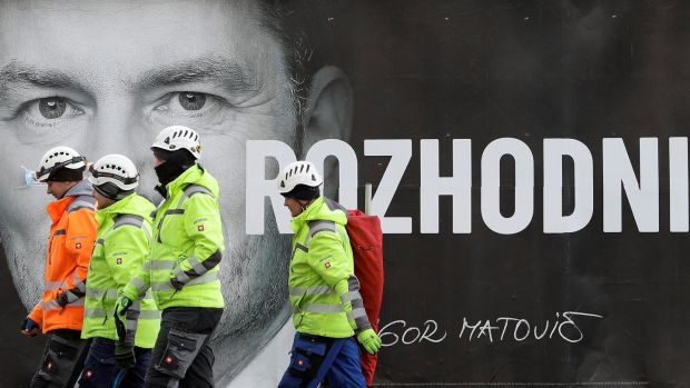 "Workers walk past an election poster of Ordinary People and Independent Personalities leader Igor Matovic, ahead of the country's parliamentary election, in Bratislava. The poster reads: ""Decide"". Photograph: David Cerny/Reuters"
