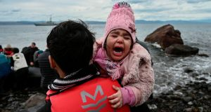REFUGEE CRISIS: A child cries as a dinghy with 54 Afghan refugees lands ashore the Greek island of Lesbos. Groups of refugees are heading towards the EU after Turkey said it would not abide by a deal to stop them reaching Europe. Photograph: Aris Messinis via Getty Images