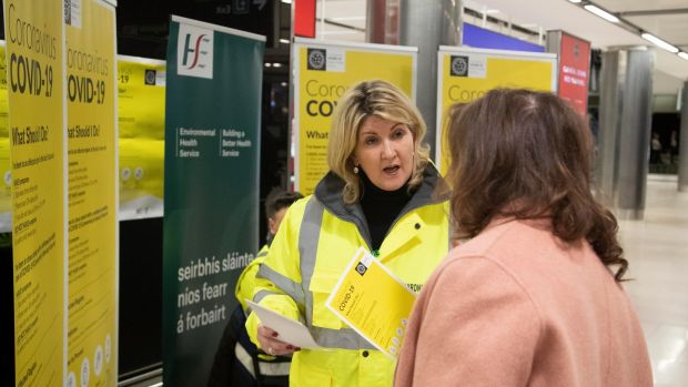 Staff handing out advice leaflets at the Coronavirus/COVID-19 stand in Dublin Airport. Photograph: Colin Keegan, Collins