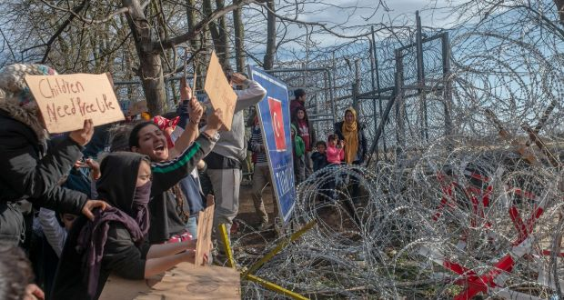 Migrants hold placards as they demonstrate while waiting at the buffer zone in front of the Pazarkule crossing on the Greece-Turkey border on Tuesday.Photograph: Bulent Kilic/AFP via Getty