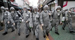 South Korean army soldiers wearing protective gears spray disinfectant as a precaution against Covid-19 at a shopping street in Seoul, South Korea, on Wednesday. Photograph: AP