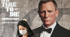 A woman wearing a facemask amid fears of the spread of Covid-19 walks past a poster for the James Bond movie No Time to Die. Its release has been delayed to November. Photograph: Mladen Antonov/AFP