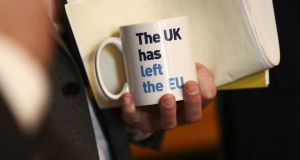 An attendee holds a mug  during a news conference unveiling coronavirus emergency plans inside Number 10 Downing Street in London. Photograph: Simon Dawson/Bloomberg
