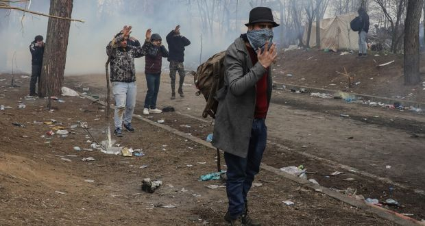 Migrants shelter from teargas fired from Greek border guards at Pazarkule border as they attempt to enter Greece from Turkey. Photograph: Osman Orsal/Getty
