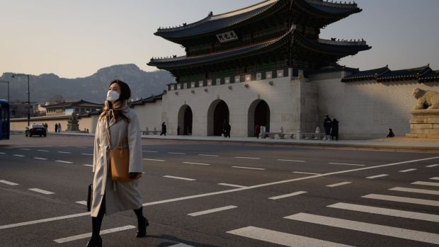 "Pedestrians wearing face masks, amid concerns about the spread of the COVID-19 novel coronavirus, cross a road in front of the Gyeongbokgung palace in central Seoul on March 6, 2020. - Seoul threatened to retaliate on March 6 over what it called Tokyo's ""irrational"" plan to quarantine arrivals from South Korea over the coronavirus outbreak, turning the scientific issue into a diplomatic row. (Photo by Ed JONES / AFP) (Photo by ED JONES/AFP via Getty Images)"