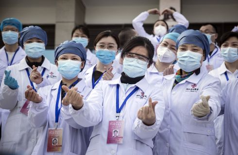 A JOB WELL DONE: Medical professionals pose for photos as the last batch of Covid-19 patients are discharged from Wuchang Fang Cang makeshift hospital in Wuhan, Hubei province, China. As the number of coronavirus patients drops in the country, the city has closed 11 temporary hospitals. Photograph: Stringer/Getty Images