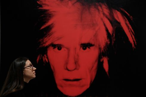 WARHOL'S WORLD: A gallery assistant poses as she views Self-Portrait by Andy Warhol, which forms part of a retrospective of works by the late American artist, at the Tate Modern in London. Photograph: Toby Melville/Reuters