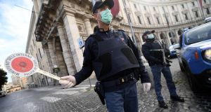 Italian police carry out checks after further restrictions amid the coronavirus emergency lockdown in Rome on Thursday. Photograph: Ettore Ferrari/EPA