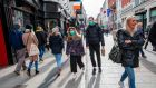 A couple wear surgical masks while shopping  on  Grafton Street, Dublin. The longer the health crisis continues the bigger the economic impact. Photograph: Paul Faith / AFP via Getty Images