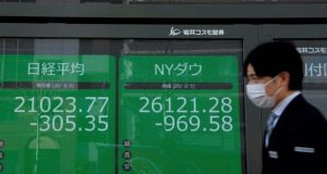 A pedestrian walks past quotation boards displaying a share price from the Tokyo Stock Exchange. Photograph: Kazuhiro Nogi/AFP