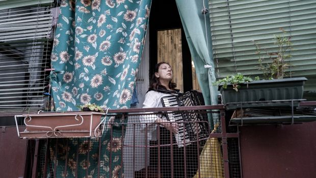 A woman plays music from her balcony in Milan. Photograph: New York Times